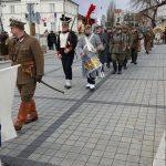 Przemarsz przestawicieli historycznych jednostek wojskowych na tle Urzędu stanu cywilnego w Piasecznie