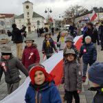 Przemarsz dzieci niosących flagę Polski na tle Urzędu stanu cywilnego